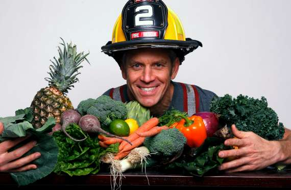 Engine 2 Diet founder poses with a bounty of vegetables
