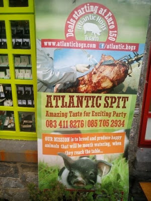 "Top image shows a skewered pig's corpse charred and sliced, while bottom image shows a happy piglet in clover. Reads, ""Atlantic Spit: Amazing Taste for Exciting Part. Our mission is to breed and produce happy animals that will be mouth watering, when they reach they table..."""