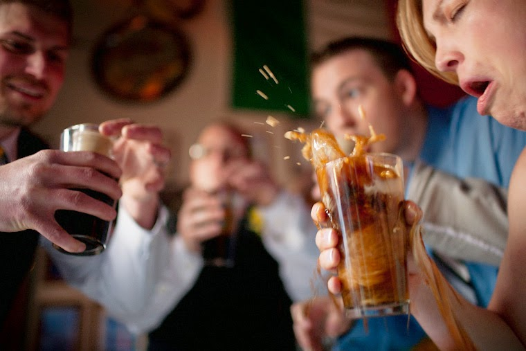 A couple drops a shot of Baileys Irish Cream into a pint of Guiness