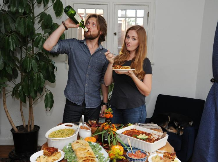 White-presenting couple standing in front of a food spread. Man is throwing back a large bottle of alcohol.